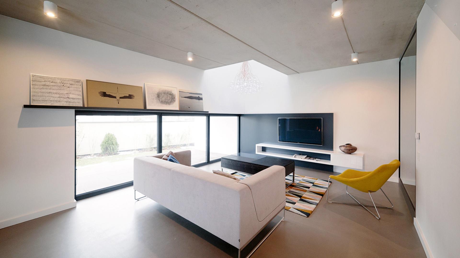 Dom został zaprojektowany dla czteroosobowej rodziny. Jego mieszkańcy to ludzie ceniący wygodę i wysoką jakość materiałów. Lubią otaczać się niebanalnymi przedmiotami, dobrze czują się w oszczędnej stylistyce. Wnętrze podzielone jest na strefy, które przenikają się, tworząc spójną przyjazną przestrzeń. Realizacja: Kamil Salanyk, BASK grupa projektowa. Fot. Archiconnect.pl