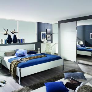 Moita to nowoczesna kolekcja mebli w wersji biel na wysoki połysk. Lustrzane powierzchnie powiększą wnętrze niewielkiej sypialni. Drzwi szafy oparte są na systemie suwnym co dodatkowo oszczędza przestrzeń. Fot. Agata Meble.