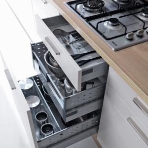 Podczas gotowania zawsze potrzebne są dodatkowy garnek, rondel czy chochla. Dobrze je mieć w zasięgu ręki, np. w szufladach pod płytą grzejną. Na zdjęciu: meble firmy Black Red White. Przegródki w szufladach ułatwiają posegregowanie przedmiotów. Fot. Black Red White.
