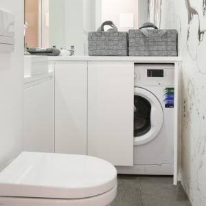 Wąska łazienka w bieli ma białe ściany oraz praktyczny schowek na pralkę. Projekt: Karolina Łuczyńska. Fot. Bartosz Jarosz.