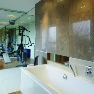Ściany łazienki wyłożono imitującymi kamień płytami gresu w kolorze chłodnego brązu, podłogę - jasnym gresem i deskami tekowymi. Fot. Tomasz Markowski.
