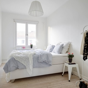 W sypialni urządzonej na biało sprawdzą się delikatne, pastelowe kolory, które ożywią wnętrze, ale nie zdominują go. Dobrym wyborem będą także subtelne tkaniny, jak koronki czy poduszki z falbankami. Fot. Standshem.