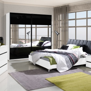 Kolekcja Saragossa w kolorze biały i czarny połysk. W skład kolekcji wchodzą łóżko, szafki nocne, komoda oraz szafy. Fot. Agata Meble.