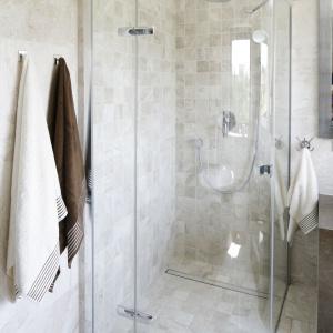 Elegancka kabina prysznicowa jest niemal niewidoczna na tle ściany w beżowej płytkach. Fot. Bartosz Jarosz.