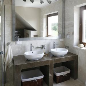 Duże lustro w ramie optycznie powiększa salon kąpielowy w ciepłych beżach. Fot. Bartosz Jarosz.