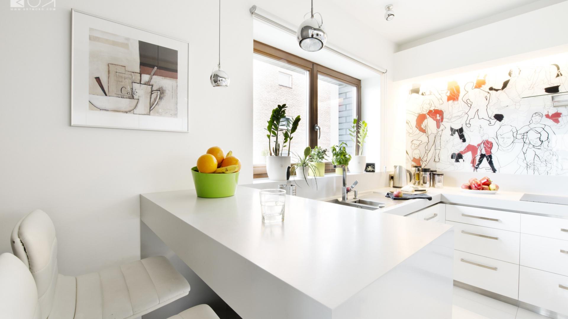 W kuchni przełamano biel i stal kolorową grafiką, która każdego poranka pozytywnie rozbudza domowników. Komplet białych krzeseł wraz ze szklanym stołem zostały usytuowane pomiędzy salonem a kuchnią tworząc przestrzeń jadalni. Realizacja: Monika Skóbel, Pracownia projektowa artMOKO. Fot. Archiconnect.pl