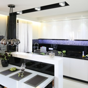Kuchnia urządzona jest w biało-czarnej kolorystyce, dzięki czemu jest nowoczesna, ale i elegancka. Charakteru dodaje jej mozaika nad blatem oraz oryginalna grafika. Projekt: Małgorzata Mazur. Fot. Bartosz Jarosz.