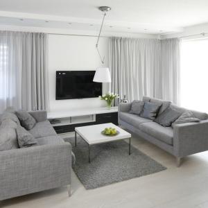 W eleganckim salonie dominują szarości. Telewizor zawieszony na ścianie można oglądać siedząc na jednej z dwóch kanap. Projekt: Karolina Stanek-Szadujko, Łukasz Szadujko. Fot. Bartosz Jarosz.