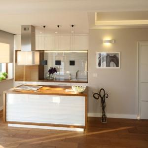 Aranżacja kuchni oparta o jasne, stonowane barwy. Biel zestawiono tutaj z szarościami oraz drewnem. Projekt: Karolina Łuczyńska. Fot. Bartosz Jarosz.