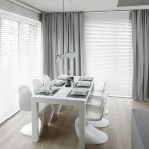 Jadalnię stanowi biały stół o prostej stylistyce z towarzyszącymi mu designerskimi pantonowskimi krzesłami. Projekt: Karolina Stanek-Szadujko i Łukasz Szadujko. Fot. Bartosz Jarosz.