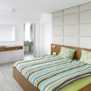 Biało-szara sypialnia z elementami drewna. Ścianę za łóżkiem wykończono miękkimi panelami, które zapewniają wygodę podczas siedzenia. Projekt: Dominik Respondek. Fot. Bartosz Jarosz.