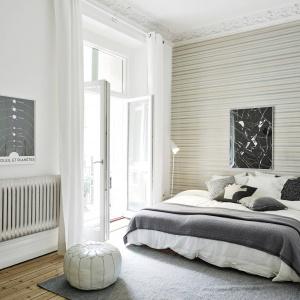 Sypialnia stylizowana na skandynawską nie zawsze musi być cała biała. Ożywić ją można ciekawą tapetą, umieszczoną na ścianie za łóżkiem. Fot. Standshem.