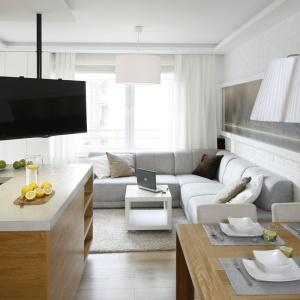 W otwartej strefie dziennej salon płynnie łączy się z kuchnią. Obie strefy optycznie oddzielają użyte tu materiały drewno - w kuchni i cegła - w salonie. Projekt: Małgorzata Mazur. Fot. Bartosz Jarosz.