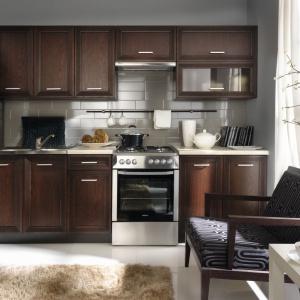 Meble na jedną ścianę mogą być również utrzymane w bardziej tradycyjnej formie. Tutaj propozycja w ciepłym, czekoladowym kolorze drewna, z klasycznymi frezowaniami i ozdobnymi uchwytami. Fot. Black Red White.