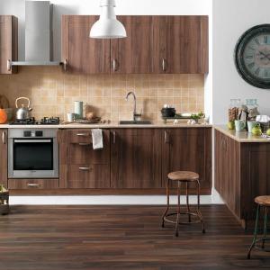 Propozycja z pionowym rysunkiem drewna w ciepłym kolorze wpasowana we wnękę w ścianie. Dodatki w postaci dużego zegara ze wskazówkami i vintage'owych stołków nadają kuchni klimat vintage. Fot. Castorama.