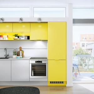 Mały aneks kuchenny wpasowany w przestrzeń pomiędzy drzwiami, ciągiem komunikacyjnym a jadalnią. Meble są proste, minimalistyczne, ale ciekawa kompozycja kolorów i połysku z matem sprawia, że kuchnia prezentuje się bardzo interesująco. Fot. HTH.