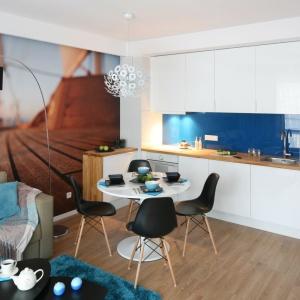 Ścianę nad blatem pokryto niebieskim lacobelem, który harmonizuje z dywanem w salonie. Projekt: Anna Maria Sokołowska. Fot. Bartosz Jarosz.