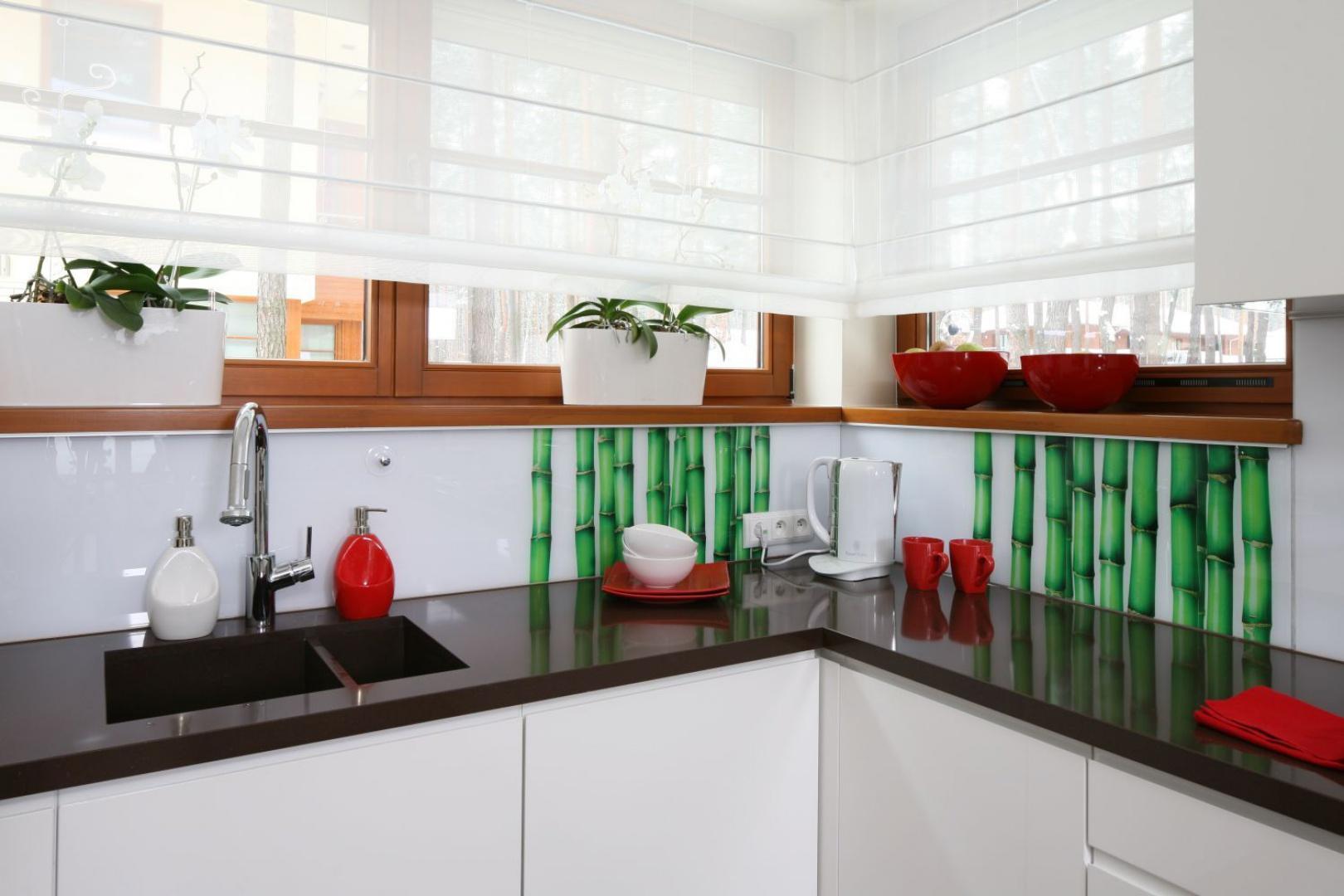 Kolorystyczny akcent w tej kuchni wprowadzają czerwone akcesoria oraz fototapeta z zielonymi bambusami nad blatem. Projekt: Katarzyna Mikulska-Sękalska. Fot. Bartosz Jarosz.