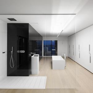 Bardzo duża, przestronna łazienka została urządzona w czerni i bieli, z ocieplającym je kolorem jasnego drewna. Strefę prysznica przeszklono przeźroczystym szkłem. Projekt: Marie-Pierre Auger Bellavance, Studio Practice. Fot. Adrien Williams & Gorgin S. Fazli.