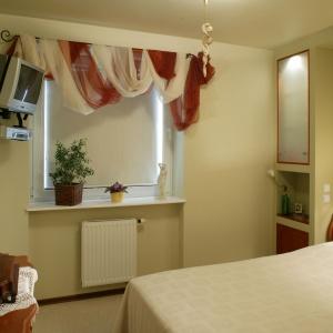 Sypialnia zaaranżowana w tradycyjnym stylu. Dekoracyjne, fantazyjnie udrapowane firanki to hit aranżacyjny sprzed kilku lat. Projekt: Elżbieta Wierzbicka.