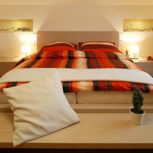 Jasna sypialnia na poddaszu. Drewniane meble, podświetlone półki z gipsokartonu oraz ławka ulokowana u podstawy łóżka wyznaczają stylistykę wnętrza. Projekt: Joanna Wysocka.