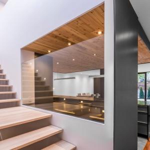 Za dużą kuchnią schowano schody, zamknięte w przeszklonej klatce schodowej. Projekt: MU Architecture. Fot. Julien Perron-Gagné.