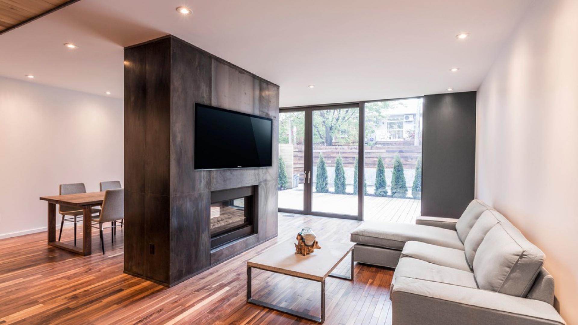 Przestrzeń otwartej strefy dziennej podzielono na dwie części za pomocą półścianki działowej, obudowanej efektownymi stalowymi panelami. Projekt: MU Architecture. Fot. Julien Perron-Gagné.