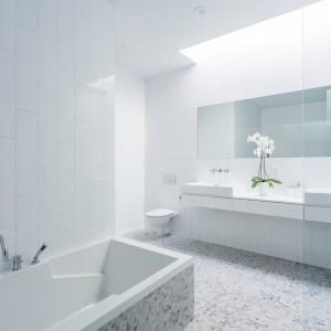 Jasny salon kąpielowy został skąpany w bieli, którą delikatnie przełamuje drobna mozaika na podłodze i wokół wanny. Projekt: MU Architecture. Fot. Julien Perron-Gagné.