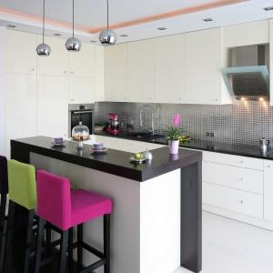 W czarno-białej eleganckiej kuchni, kolorowe hokery ustawione przy wysokim barze stanowią kolorystyczny akcent, ożywiający wystrój kuchni. Projekt: Agnieszka Żyła. Fot. Bartosz Jarosz.