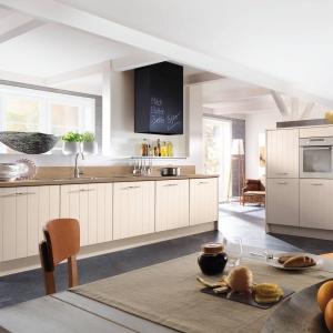 Fronty mebli kuchennych są utrzymane w jasnym kolorze i w formie naśladującej pionowe, drewniane deski. Wieńczy je blat w kolorze drewna. Fot. Impuls.