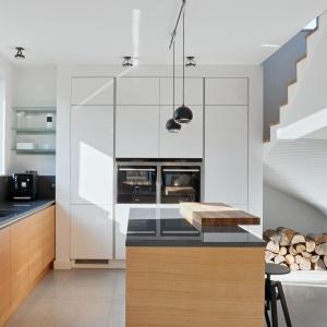 Dolna zabudowa kuchenna to gładkie, minimalistyczne fronty z poziomym rysunkiem drewna w ciepłym, miodowym kolorze. Fot. Atlas Kuchnie.