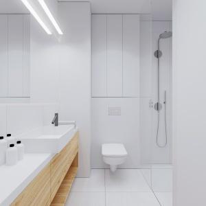 Proste formy, wszechobecna biel oraz duże lustro na ścianie nad umywalką optycznie powiększają przestrzeń niewielkiej łazienki. Projekt i wizualizacje: 081 Architekci.