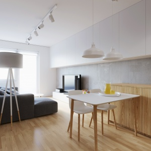 Przestrzeń salonu, kuchni i jadalni spajają wizualnie aż trzy elementy wykończenia wnętrza: płyty betonowe na ścianie, biała płytka zabudowa pod sufitem oraz jednorodna deska podłogowa. Projekt i wizualizacje: 081 Architekci.