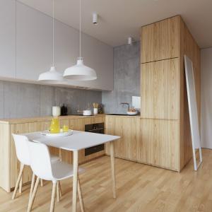 Zabudowę kuchenną wykonano w dwóch kolorach: matowej bieli na frontach górnych szafek oraz w drewnie, kolorystycznie harmonizującym z podłogą. Projekt i wizualizacje: 081 Architekci.