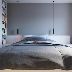 Zamiast tradycyjnych lampek nocnych, nad łóżkiem zawisły dwie nowoczesne lampy na długich oplotach. Obok łóżka zaplanowano biblioteczkę na książki do lektury przed snem. Projekt i wizualizacje: 081 Architekci.