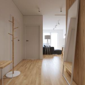 W przedpokoju ustawiono swobodnie duże lustro w białej ramie, które optycznie powiększa przestrzeń. Projekt i wizualizacje: 081 Architekci.