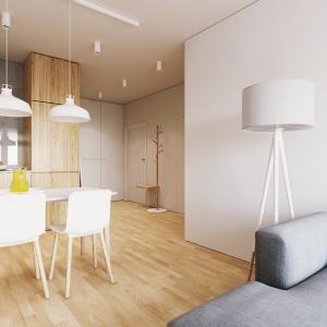 Z drewnianą zabudową kuchenną, która stanowi łącznik z przedpokojem dialog prowadzi wieszak o formie nagiego drzewka. Projekt i wizualizacje: 081 Architekci.