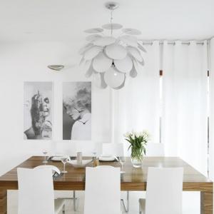 W tej jadalni biel zestawiono z ciepłym odcieniem drewna, wprowadzonym przez okienne ramy oraz solidny stół. Nad nim zawisła piękna lampa o fantazyjnej formie, złożona z licznych mniejszych elementów. Projekt: Agnieszka Ludwinowska. Fot. Bartosz Jarosz.