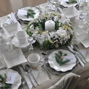 Elegancki obrus w jasnobeżowym kolorze zdobią subtelne, wyszywane wzory. Z kolorystyką obrusu harmonizują duże talerze. Oprócz tych dwóch elementów na stole króluje biel i świąteczne, zielone gałązki świerku. W środku aranżacji ułożono piękny, ręcznie robiony wianek. Fot. Tendom.pl.