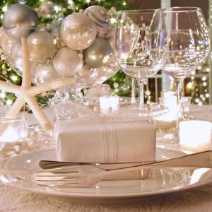 Nawet jeśli za oknem pogoda nie rozpieszcza i nie widać śniegu, stół możemy urządzić w zimowych kolorach. Biała zastawa, obrus i dekoracyjne bombki wprowadzą zimowy nastrój w każdym domu. Fot. Shutterstock.