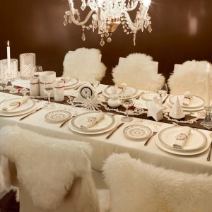 Elegancki biały obrus zdobi piękna zastawa z dekoracyjnym wzorem na brzegach talerzy. Towarzyszą jej białe dekoracje w kształcie gwiazdek i śnieżynek. Całości dopełniają futerkowe narzuty na krzesłach, wprowadzające ciepłą atmosferę. Fot. Villeroy&Boch.