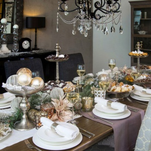 Biała porcelana, śnieżny bieżnik poprowadzony przez środek stołu, a na nim bogactwo dekoracji świątecznych. Przytulności aranżacji dodają zielone gałązki świerku, a ciekawym akcentem są złote bombki poukładane na paterach zamiast słodkości. Fot. AD Loving Home.