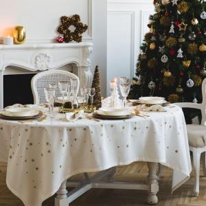 Biały obrus z motywem złotych gwiazdek zestawiono z talerzami w kolorach bieli i starego złota. Szkło zdobią delikatne, złote paski a całości dopełnia miniaturowa choinka w centrum stołu. Fot. Zara Home.