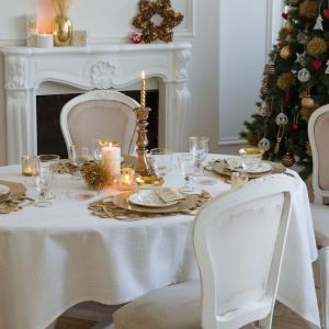 Klasyczna, elegancka aranżacja stołu na Boże Narodzenie. Biały obrus wieńczą złote podkładki, białe i złote talerze oraz delikatne kieliszki z subtelnym, złotym wykończeniem. W centrum stołu stanął solidny, tradycyjny, miedziany świecznik. Fot. Zara Home.