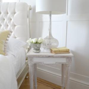 Stylowa szafka Venice idealnie komponuje się z dekoracyjnym zagłówkiem łóżka. Oba elementy wykończono w kolorze białym, dzięki temu aranżacja prezentuje się bardzo świeżo. Fot. Sweetpea & Willow.