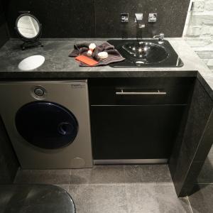 Mała łazienka z pralką i pomysłowym wykorzystaniem cegły. Powierzchnia: około 3 m². Projekt: Dominik Respondek. Fot. Bartosz Jarosz.