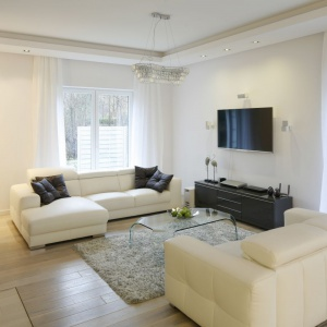 W minimalistycznym salonie dominuje biel. Telewizor zawieszono na ścianie tak, że można go oglądać z obu kanap. Projekt: Katarzyna Mikulska-Sękalska. Fot. Bartosz Jarosz.