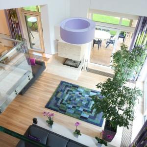 W otwartym na dwie kondygnacje salonie utrzymany w zielono-fioletowej palecie barw dywan zdobi przestrzeń parteru. Projekt: Monika i Adam Bronikowscy. Fot. Bartosz Jarosz.