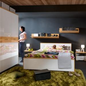 Sypialnia Bari. W projekcie wykorzystane zostało naturalne drewno dębowe, które prezentuje się szczególnie wyjątkowo na tle wykonanych na wysoki połysk frontów w kolorze bieli. Fot. Black Red White.