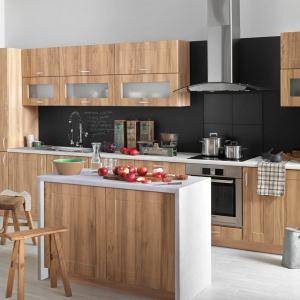 Meble w kolorze drewna zestawiono z czarną ścianą nad blatem. W ten sposób uzyskano modną, męską aranżację kuchni. Fot. Castorama, kuchnia City.